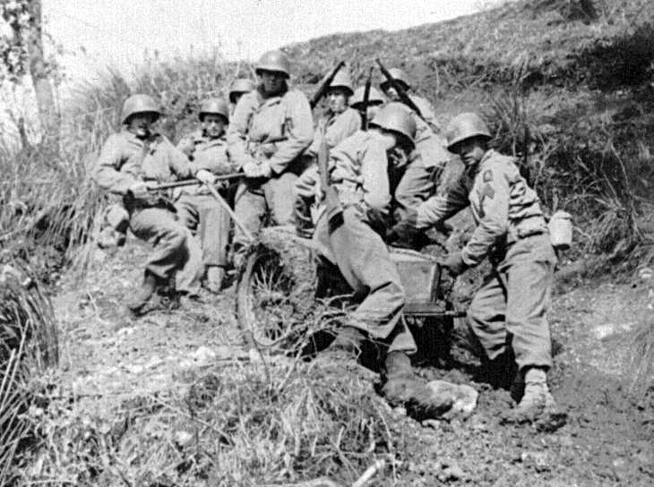 Squad of B Co 2nd Chemical Mortar Battalion hauls its 4.2 inch chemical mortar up a slope
